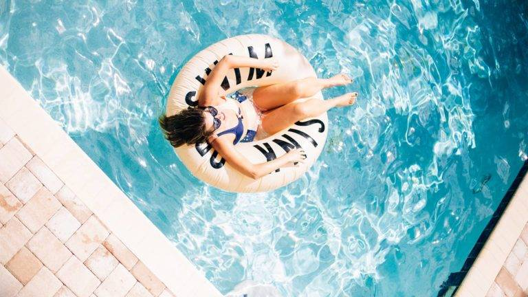 Woman relaxing on a pool float in a private pool at an Encore Resort at Reunion resort residence.