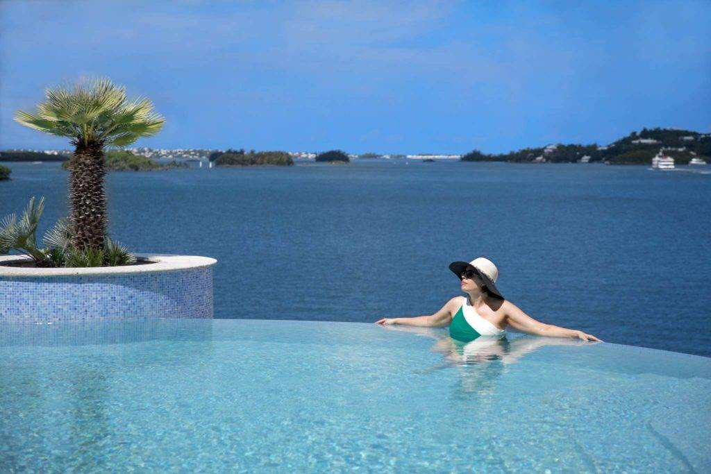 Woman in the Bermuda at Newstead Belmont Hills resort infinity pool overlooking the water.