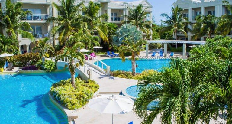 The Atrium Resort's private swimming pools surrounded by palm trees and tropical gardens.