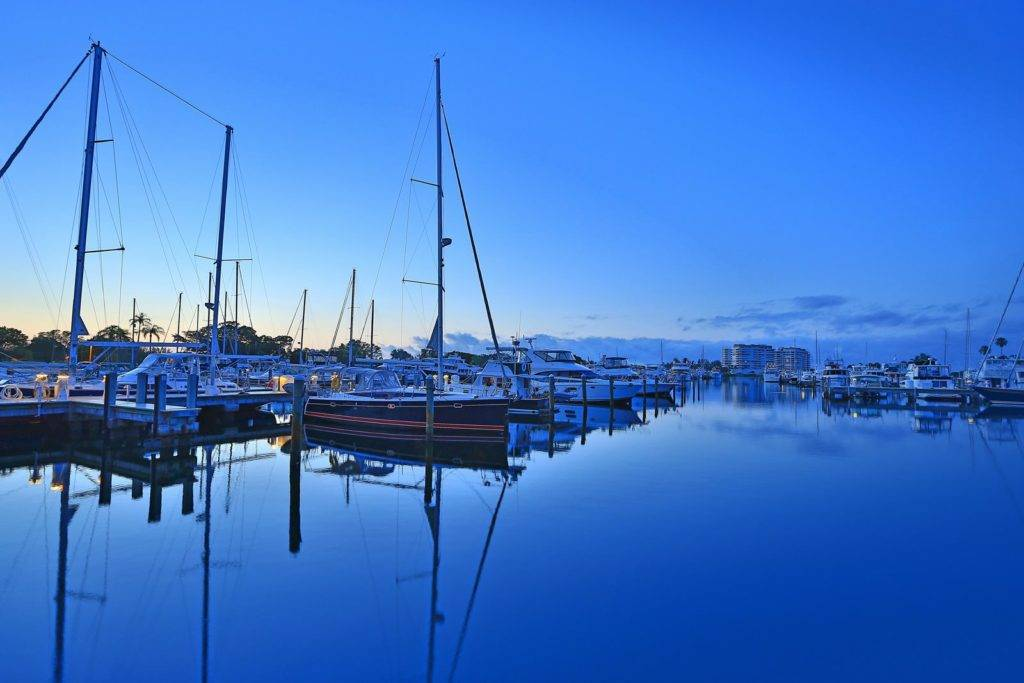 Sailboats in marina at sunrise with other boats and resort in background.