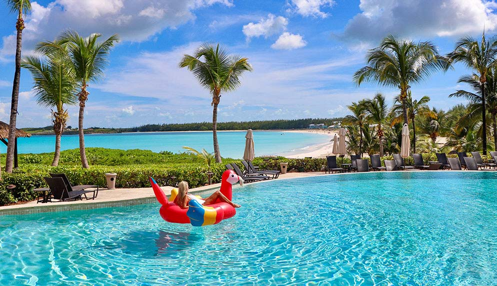 Woman relaxing in a colorful float in an infinity pool overlooking Grand Isle Resort's beach.